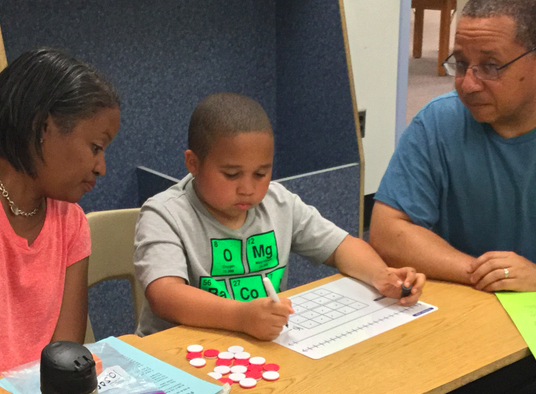 Family working on problem solving at 1st grade family night